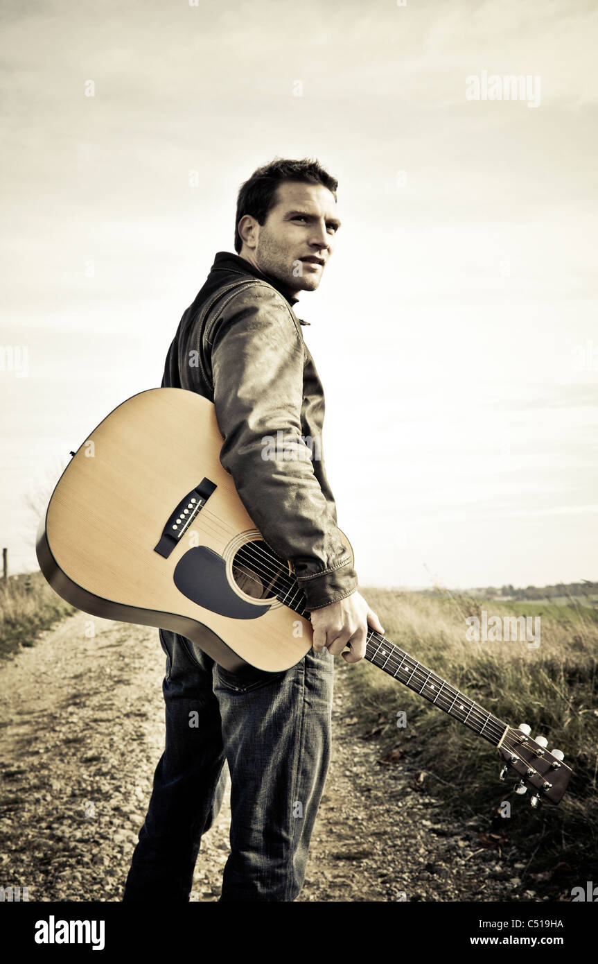 Man with a guitar walking along a road Stock Photo