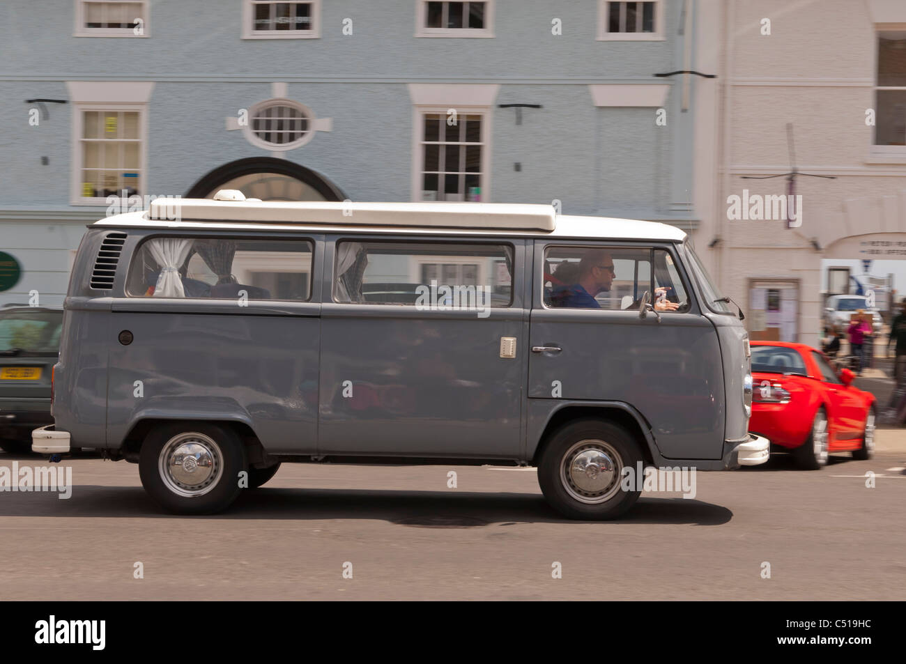 An old VW campervan driving through a UK street showing motion blur - Stock Image