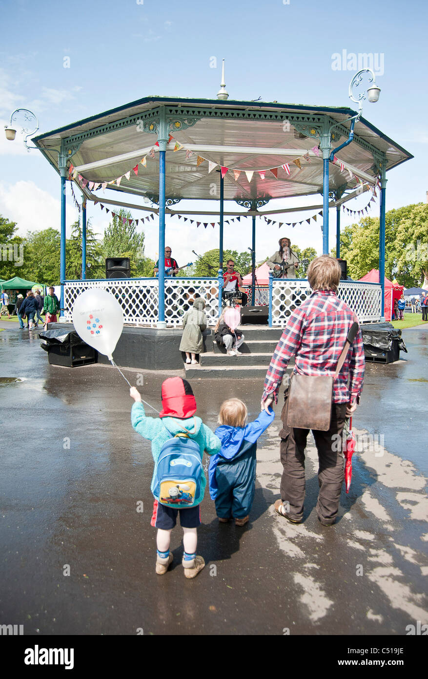 family watching musicians on a bandstand - Stock Image