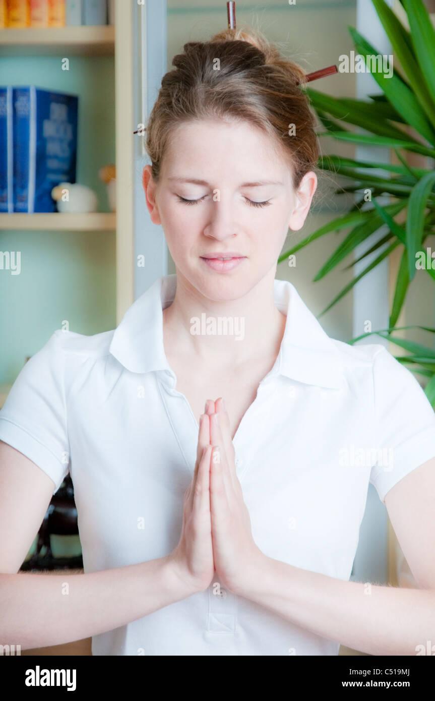 Woman meditating at home - Stock Image