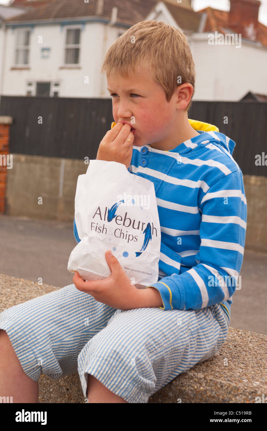 A seven year old boy eats fish & chips on the sea wall in Aldeburgh , Suffolk , England , Britain , Uk - Stock Image