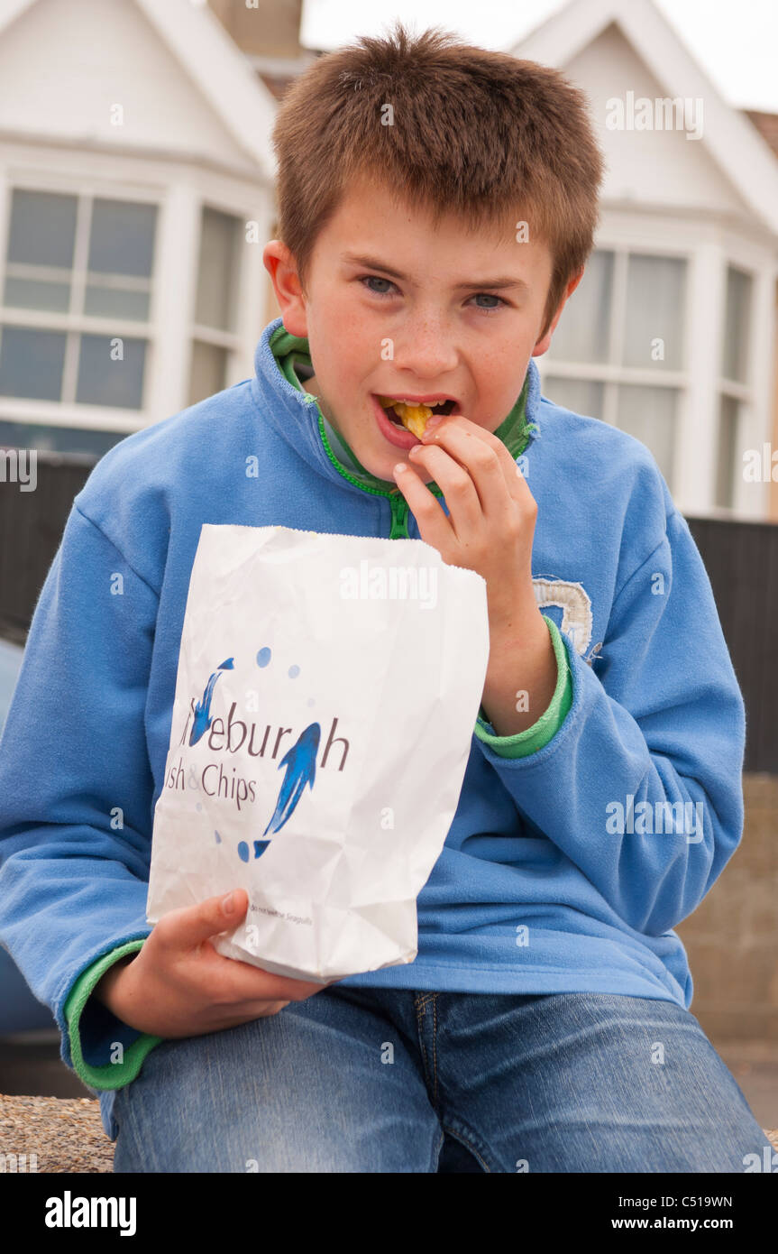 An eleven year old boy eats fish & chips on the sea wall in Aldeburgh , Suffolk , England , Britain , Uk - Stock Image
