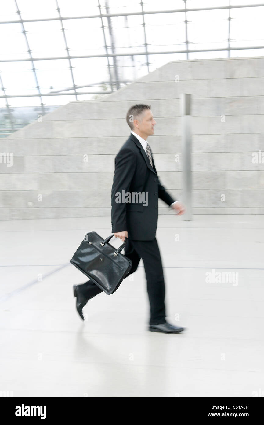 businessman walking through hall - Stock Image
