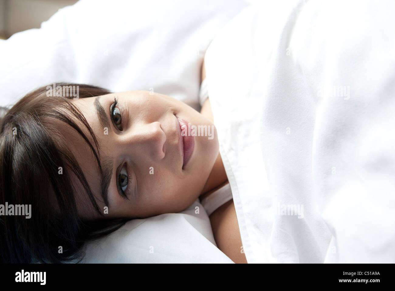 portrait of young woman lying in bed - Stock Image