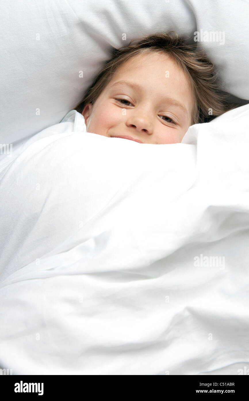 portrait of young girl in bed - Stock Image