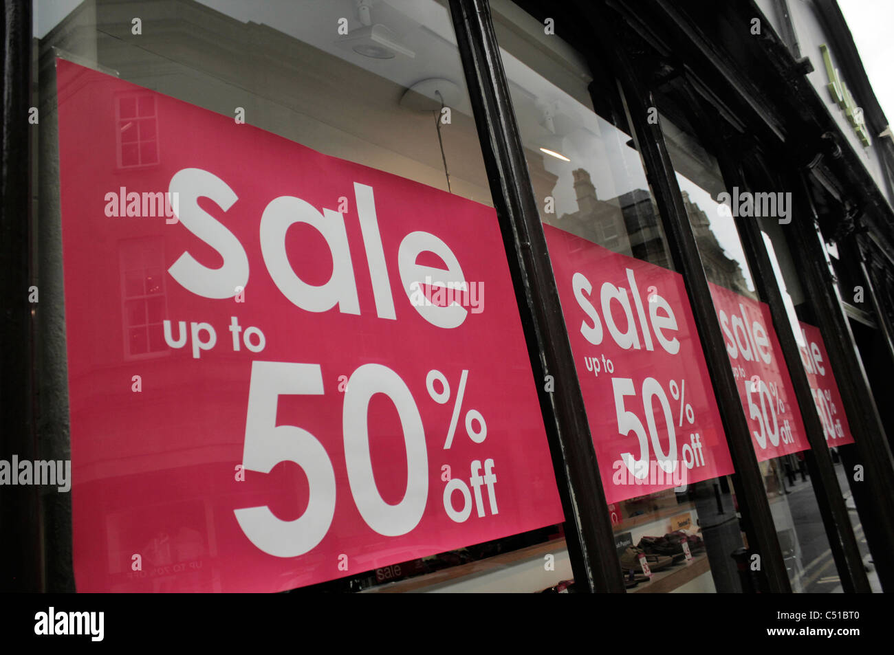 Sale signs in shop window - Stock Image