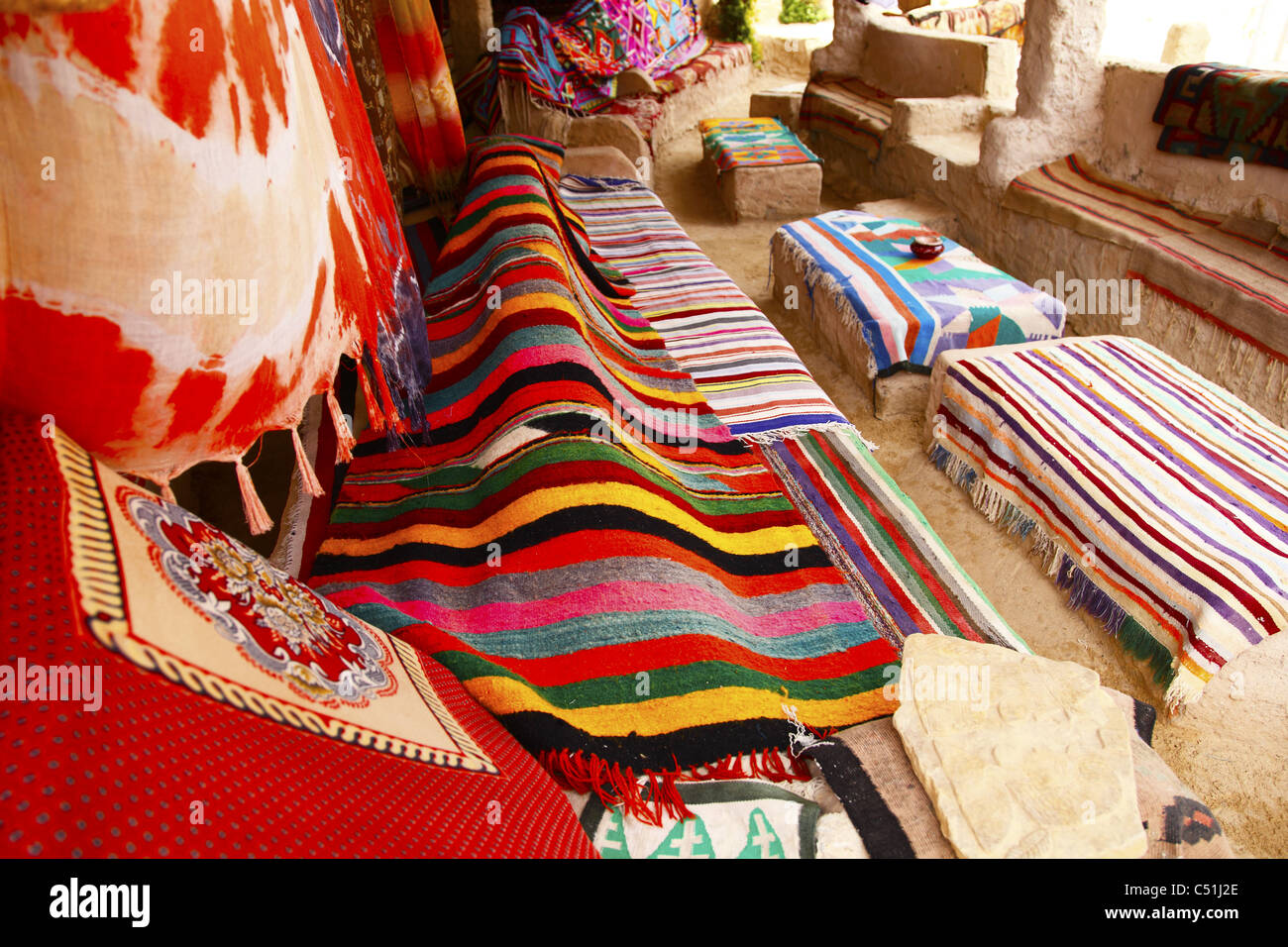 Africa, North Africa, Tunisia, Tamerza Oasis, Interior of Stall Displaying Local Cloths and Carpets - Stock Image