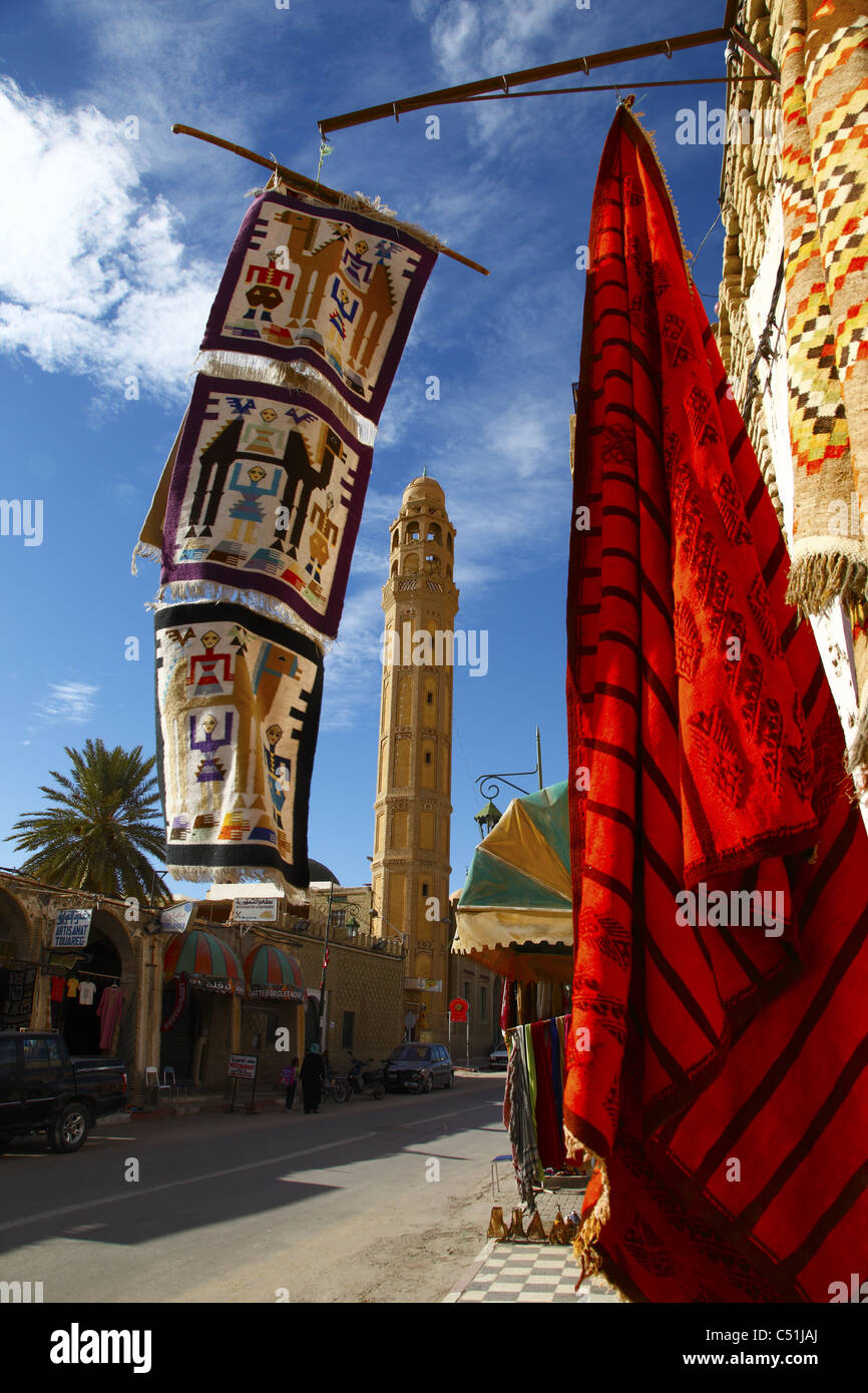Africa, Tunisia, Tozeur, Main Street with Mosque and Carpet Shop Display - Stock Image