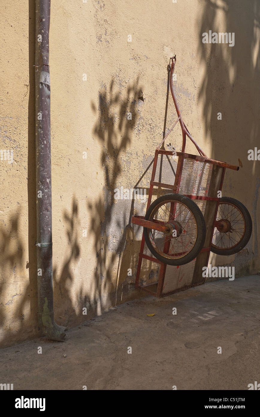 A two-wheeled cart, used for transporting goods in the village of Monterosso, Italy, hangs from the wall with dappled - Stock Image