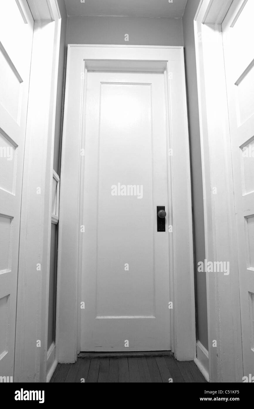 A set of closed doors ahead in black and white. Image is of the Photographer's home. - Stock Image