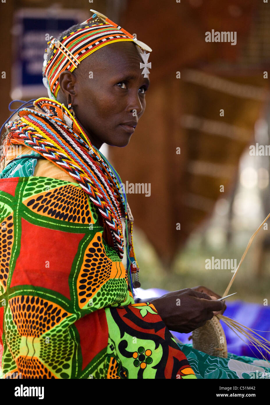A Kenyan woman in traditional dress weaving a basket Stock Photo