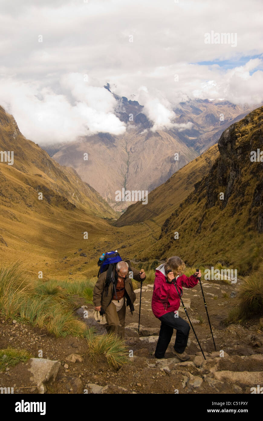 Couple approaching 13,775-foot high Warmiwanusca (Dead Woman) Pass on the Inca Trail in Peru - Stock Image