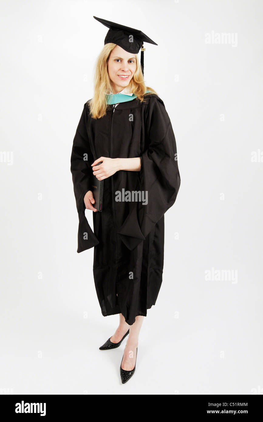 Young Woman Dressed in Graduation Gown, Holding Graduate Certificate and Smiling - Stock Image