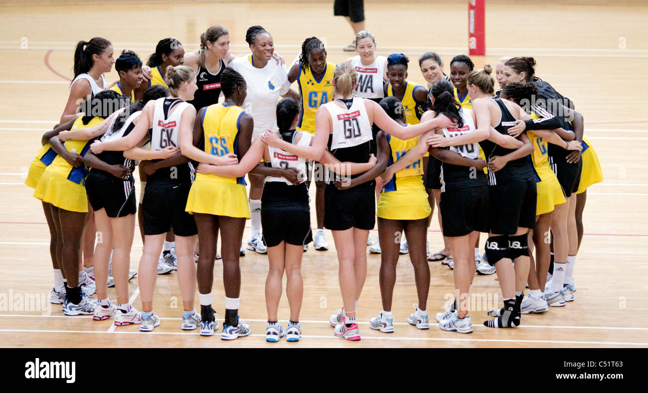Players from Barbados(yellow) and New Zealand in a group huddle after their friendly match - Stock Image