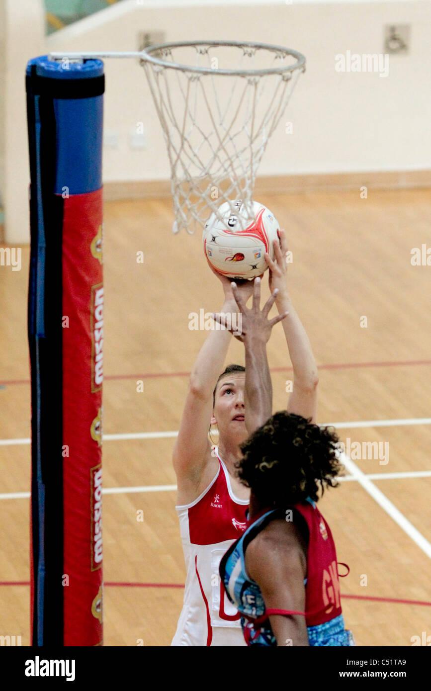 Matila Waqanidrola of Fiji(blue) attempts to block Rachel Dunn of England from shooting during a friendly match - Stock Image