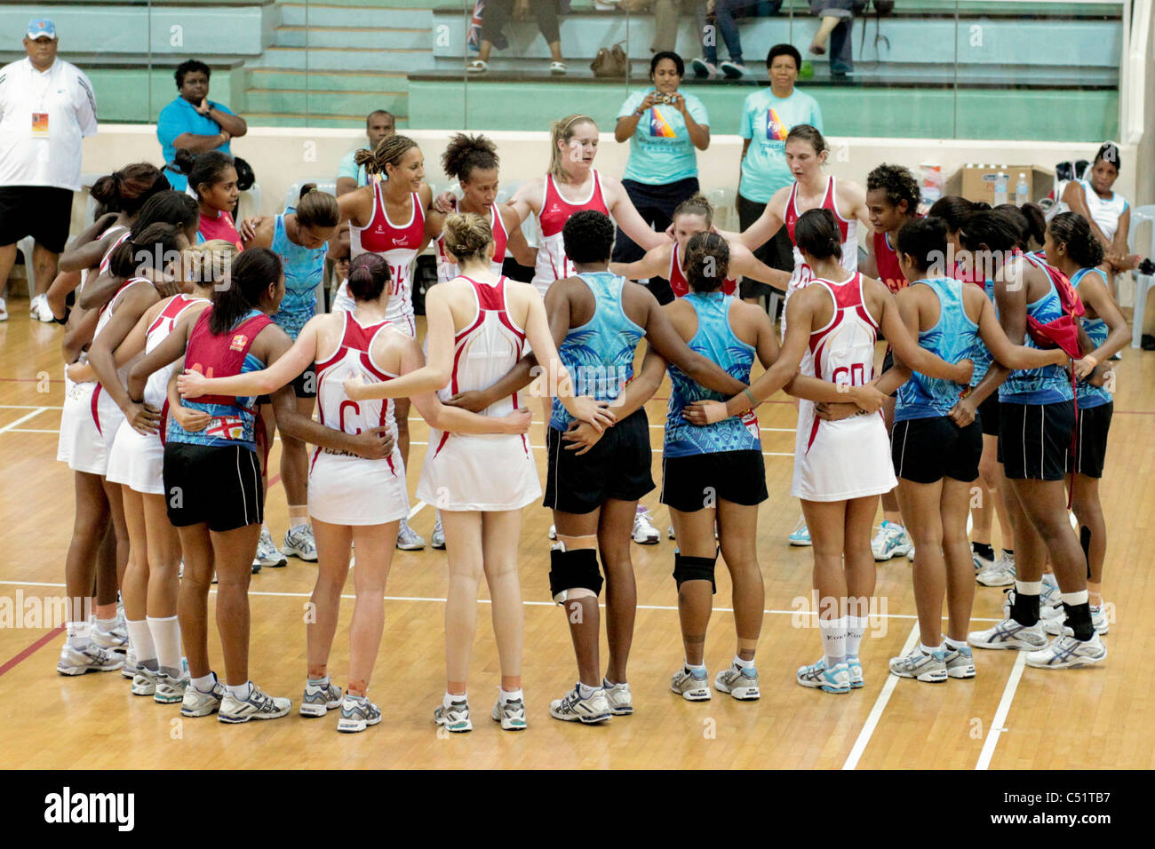 Players from England(white) and Fiji in a group huddle after their friendly match - Stock Image