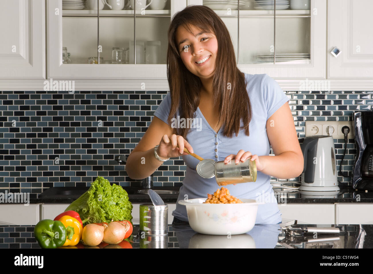 Young woman preparing food out of a can - Stock Image