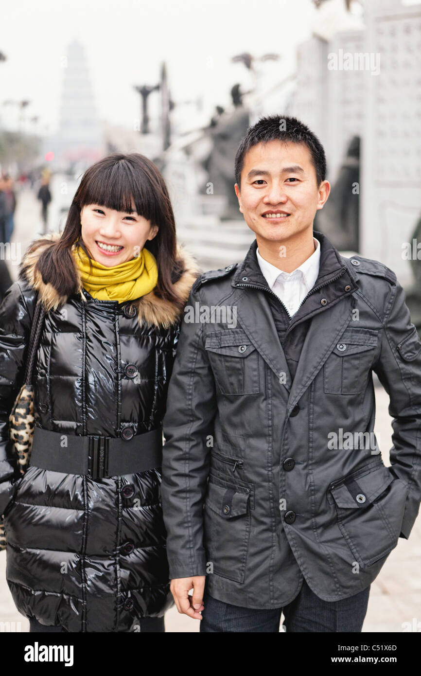 Young Chinese Couple Walking and Smiling in the Street, Xian, China - Stock Image