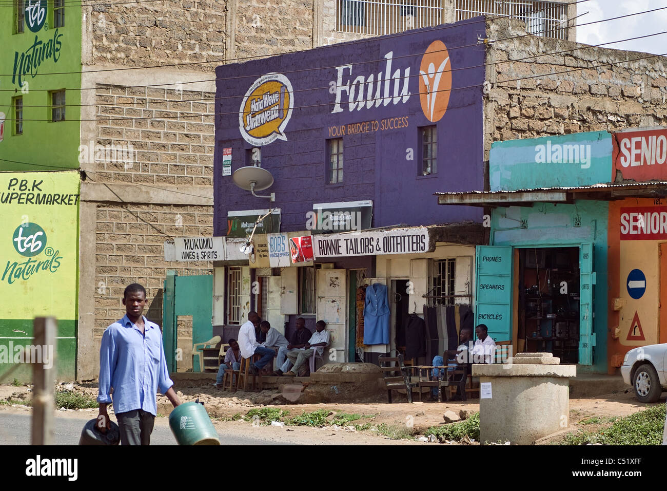 Foreground man with water containers walking past tailer shop, Nairobi slums, Kenya - Stock Image