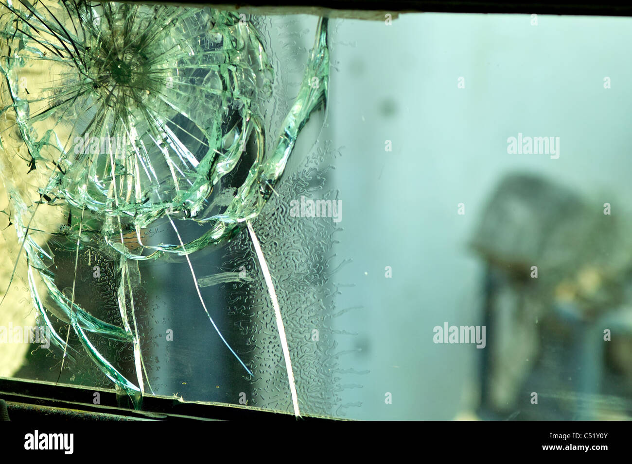bullet impact on double layer glass in side of armed vehicle - Stock Image