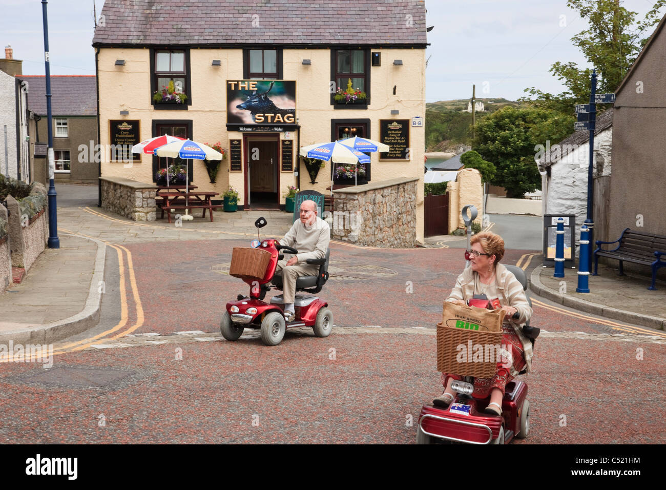 Two seniors elderly people riding on electric mobility scooters crossing a village street. North Wales, UK, Britain. - Stock Image