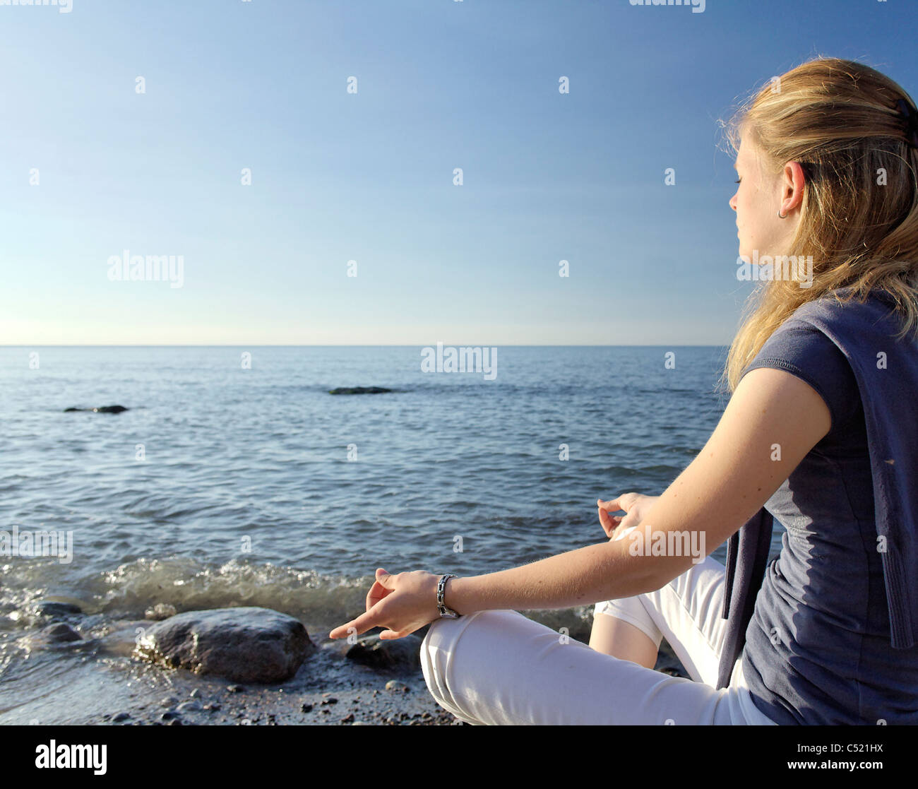 Woman meditating on the beach - Stock Image