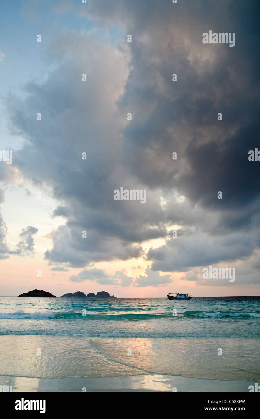 Boat at sunrise with cloud formation, Pulau Redang island, Malaysia, Southeast Asia Stock Photo
