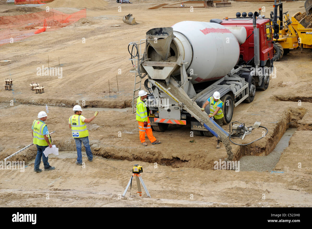Building site showing strip foundation trenches and cement mixer delivering concrete. - Stock Image