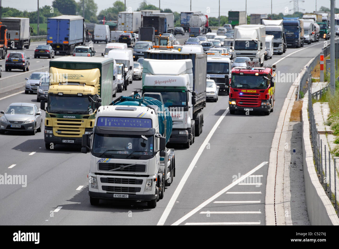 View from above looking down Essex Fire & Rescue fire brigade engine M25 motorway using hard shoulder passing - Stock Image