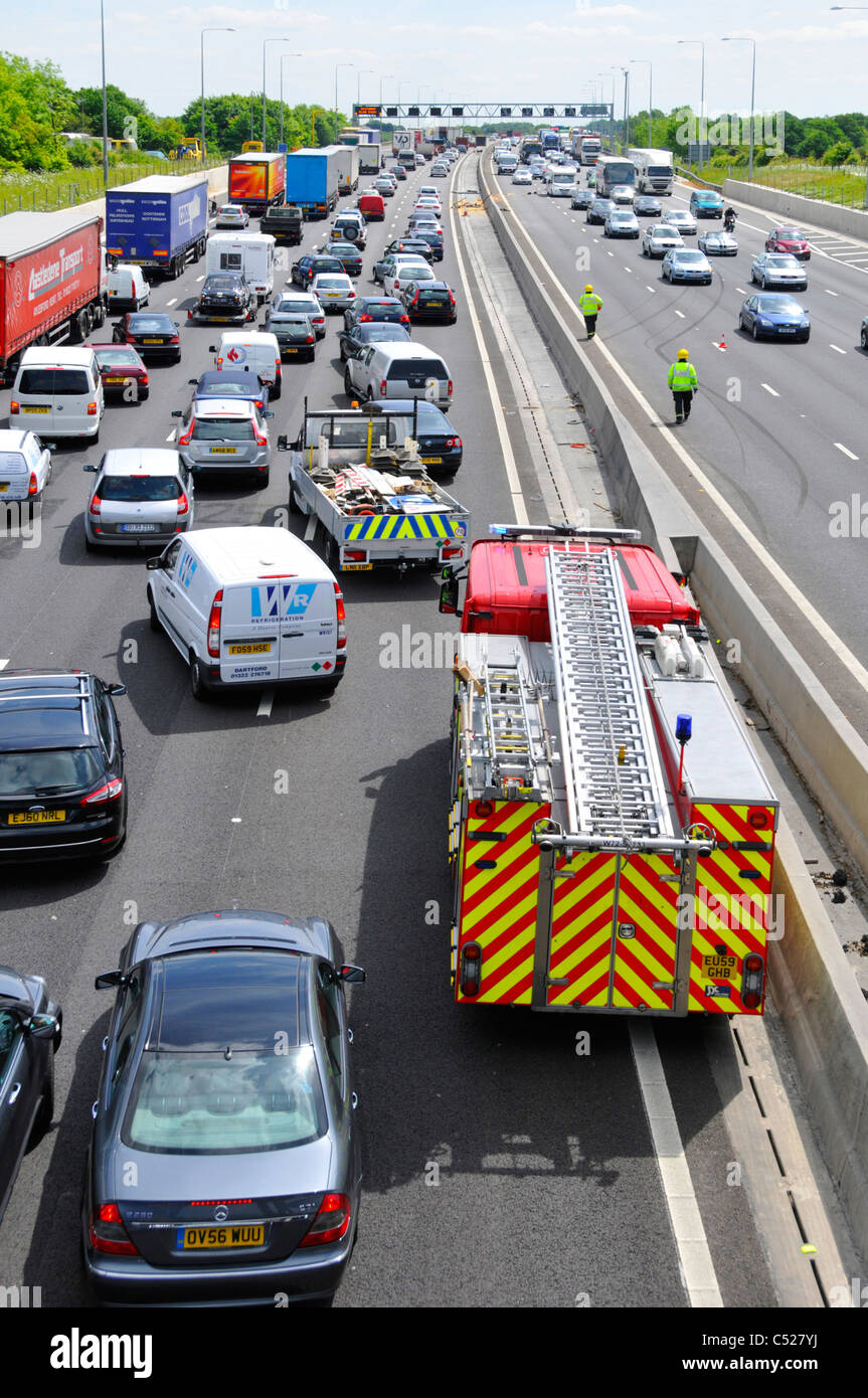 View from above looking down on busy M25 motorway traffic jam emergency services attend to two accidents on both - Stock Image