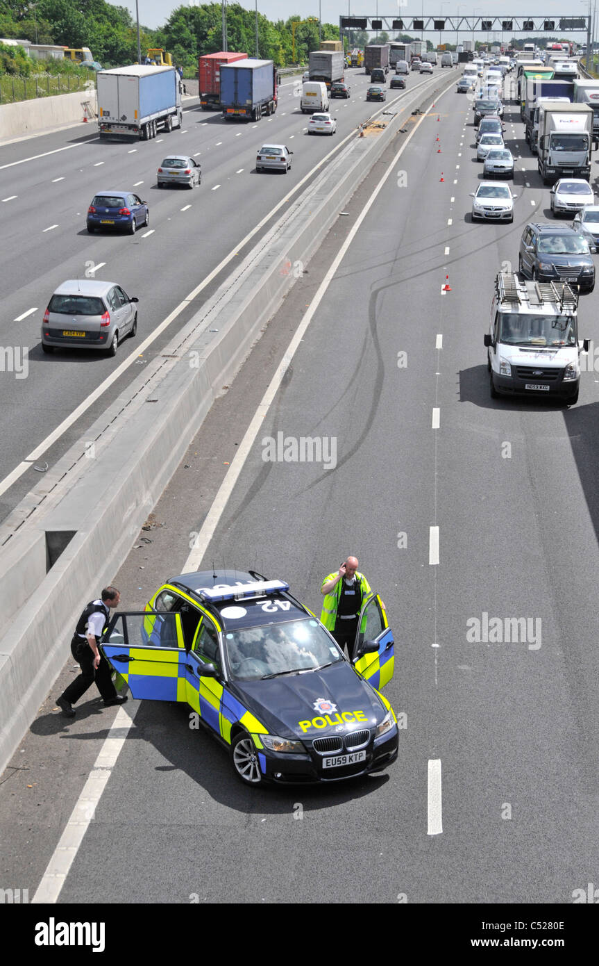 Essex police at  M25 motorway car crash accident under bridge parking in lane 4 with skid marks beyond into concrete - Stock Image