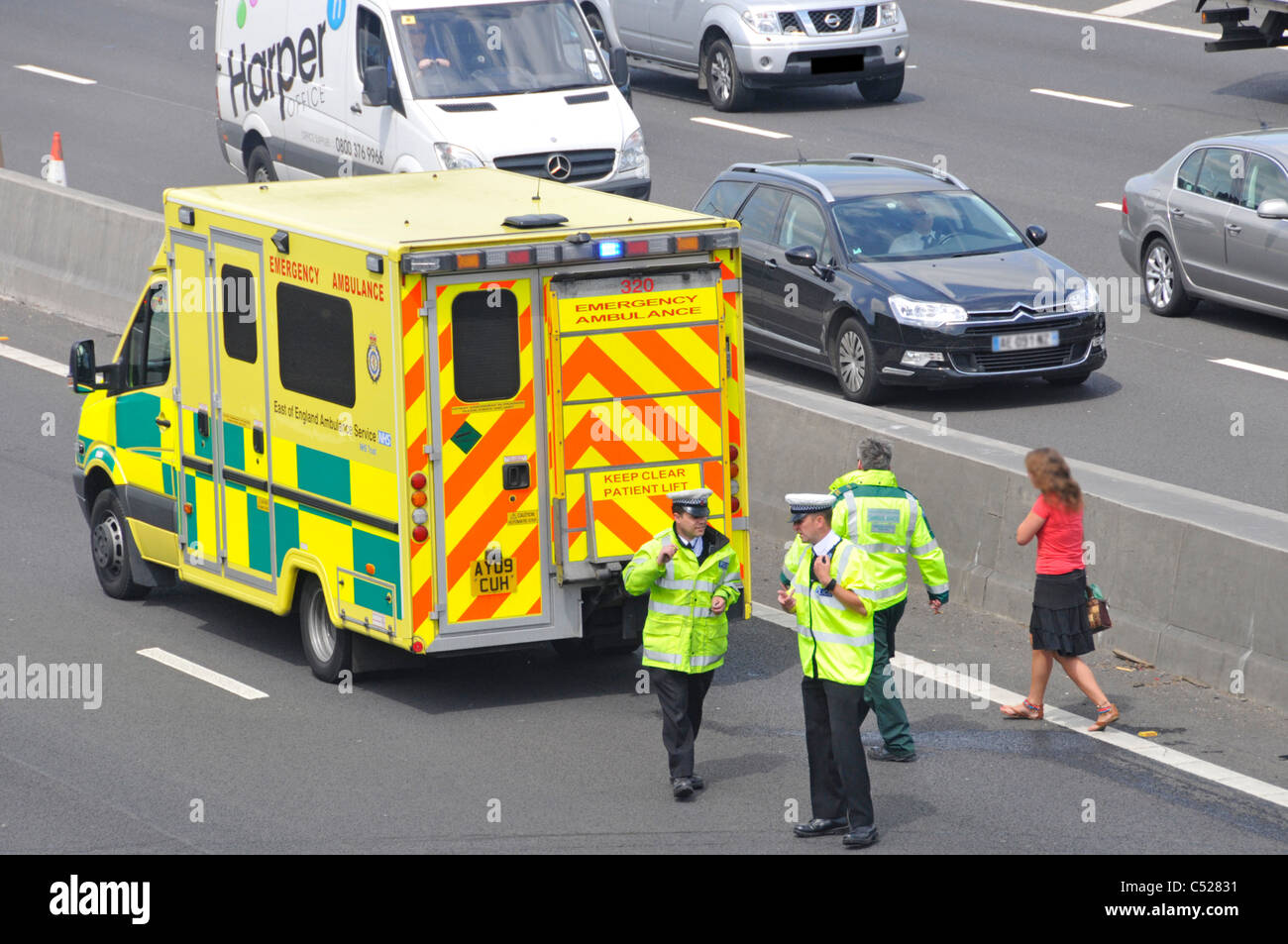 Paramedic with walking woman car crash accident victim at NHS emergency ambulance M25 motorway incident under bridge Stock Photo