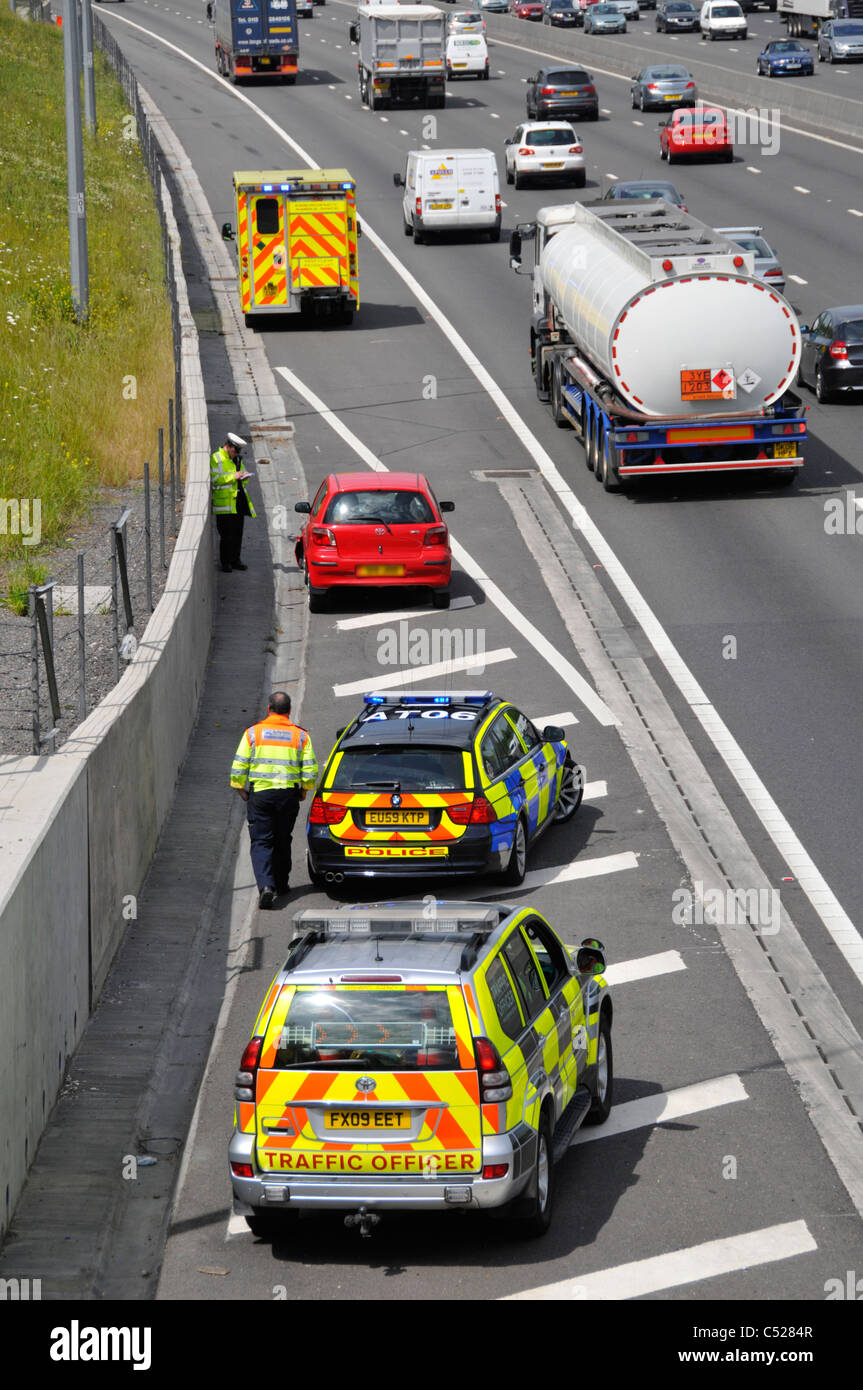 Red car involved in motorway crash moved to hard shoulder with parked emergency services vehicles - Stock Image