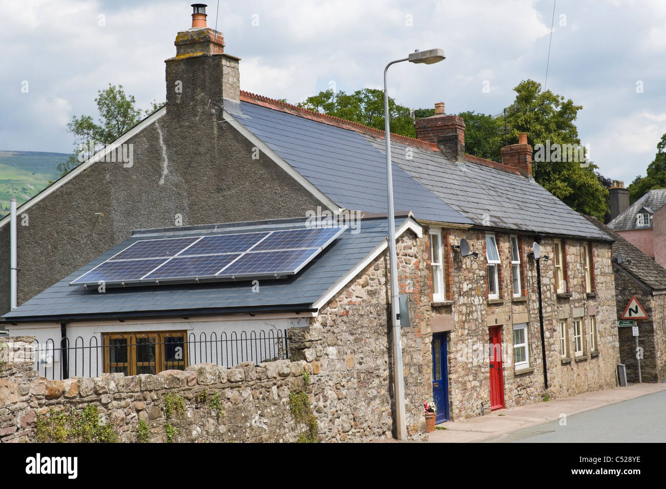 Solar panels on extension roof of terraced house in village of Llangattock Powys South Wales UK - Stock Image