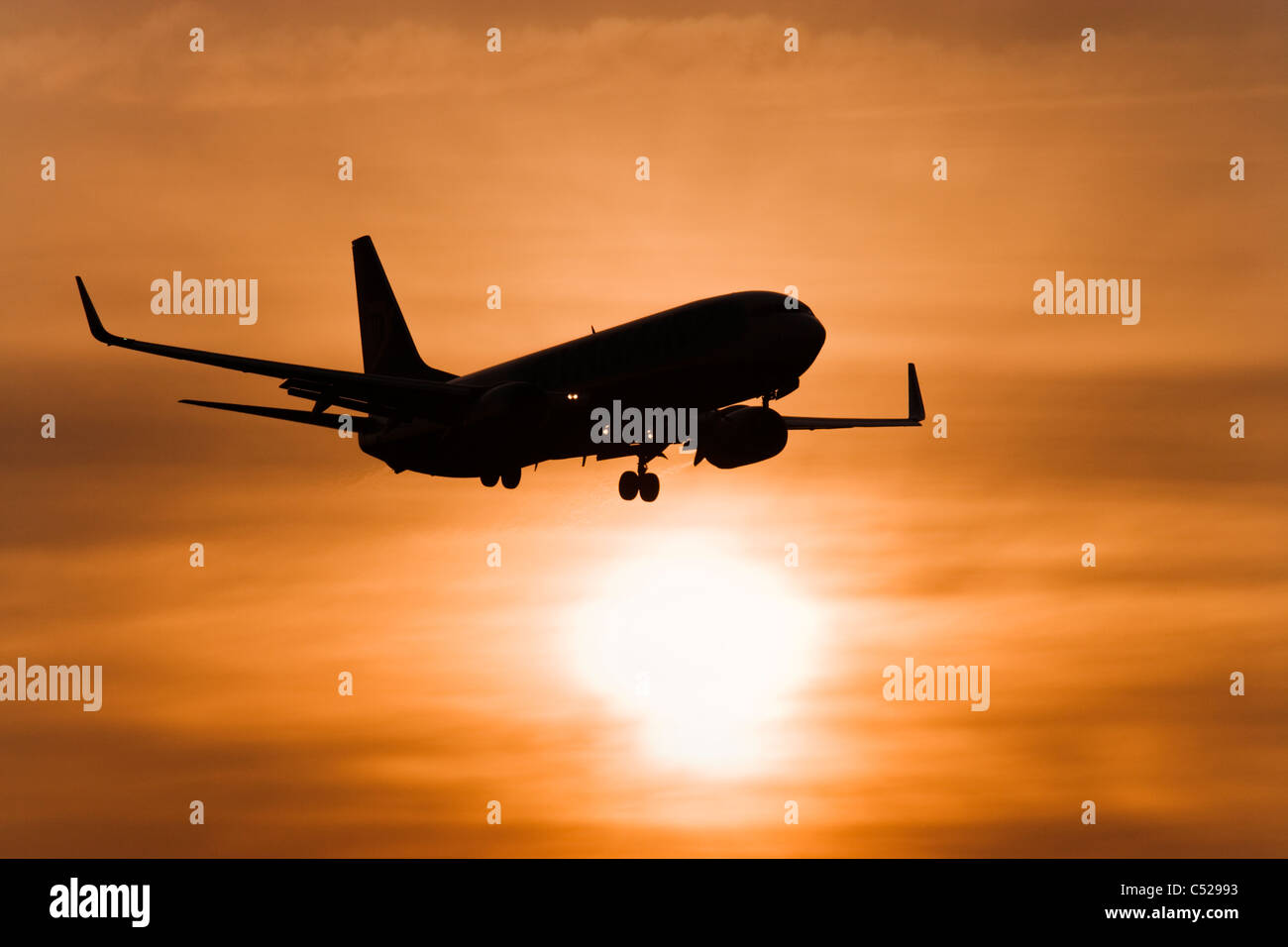 Aircraft against setting sun - Stock Image
