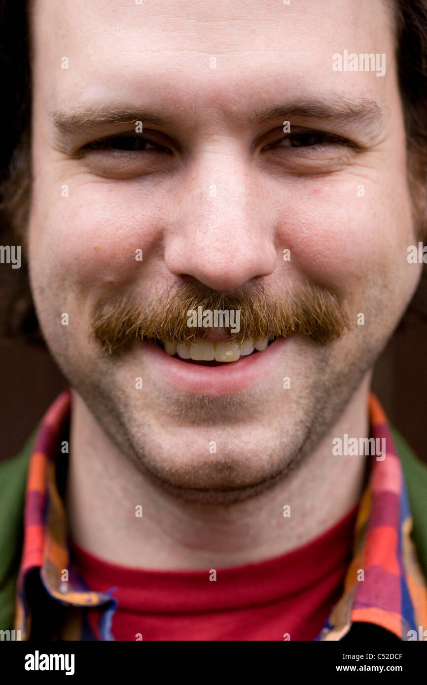 Young man in his late-twenties street portrait with moustache. - Stock Image