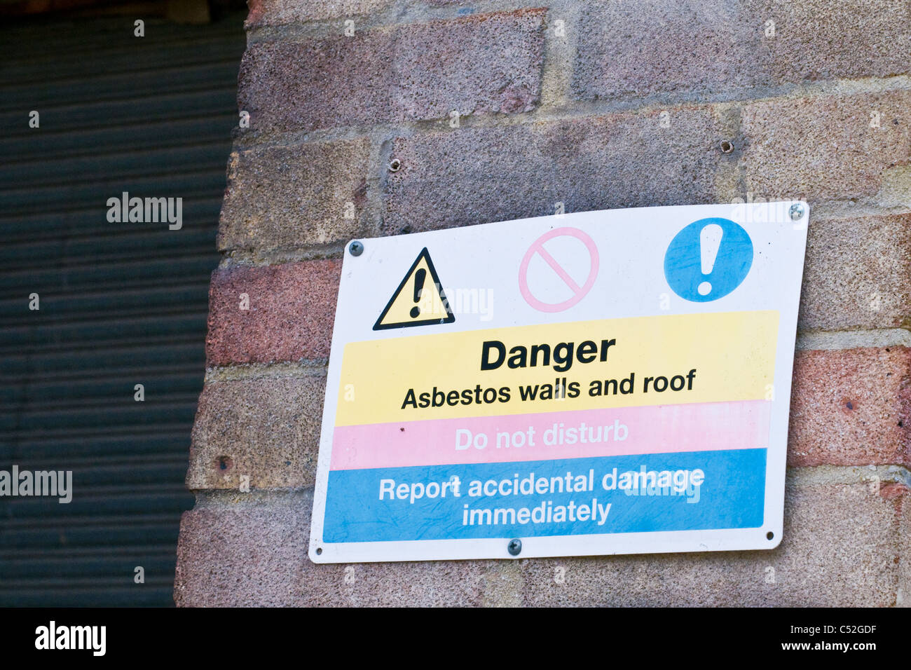 Danger Asbestos walls and roof sign, do not disturb, report accidental damage immediately - Stock Image