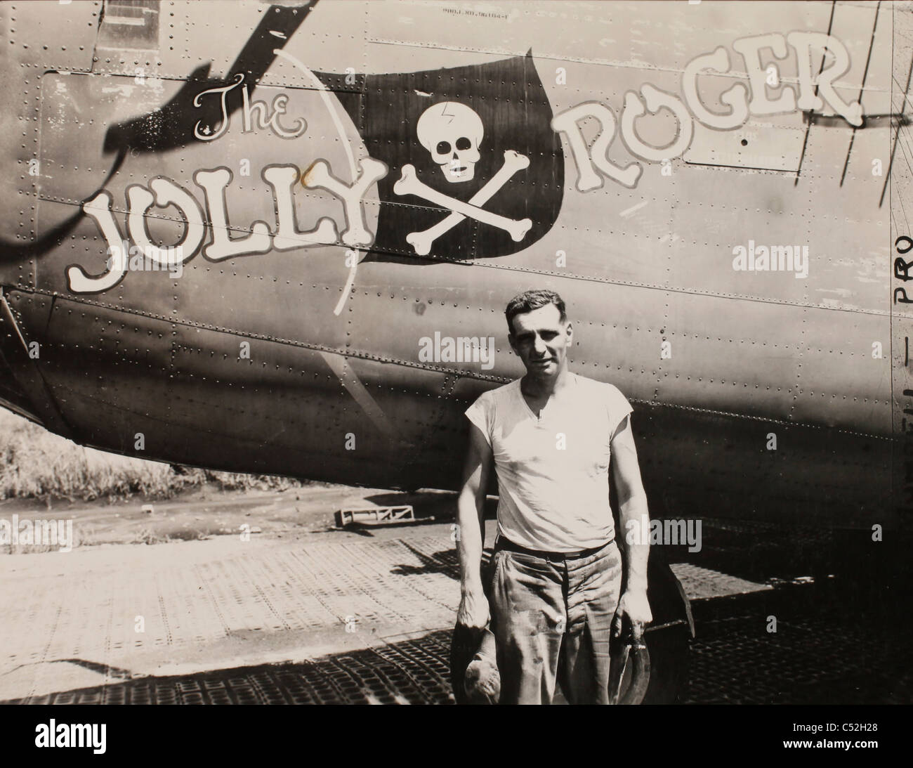 "Master Sgt. Robert Porter standing beside a b-24 liberator bomber called ""The Jolly Roger."" It is a veteran of many Stock Photo"