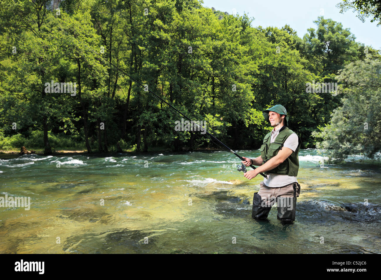 A fisherman fishing on a river Stock Photo