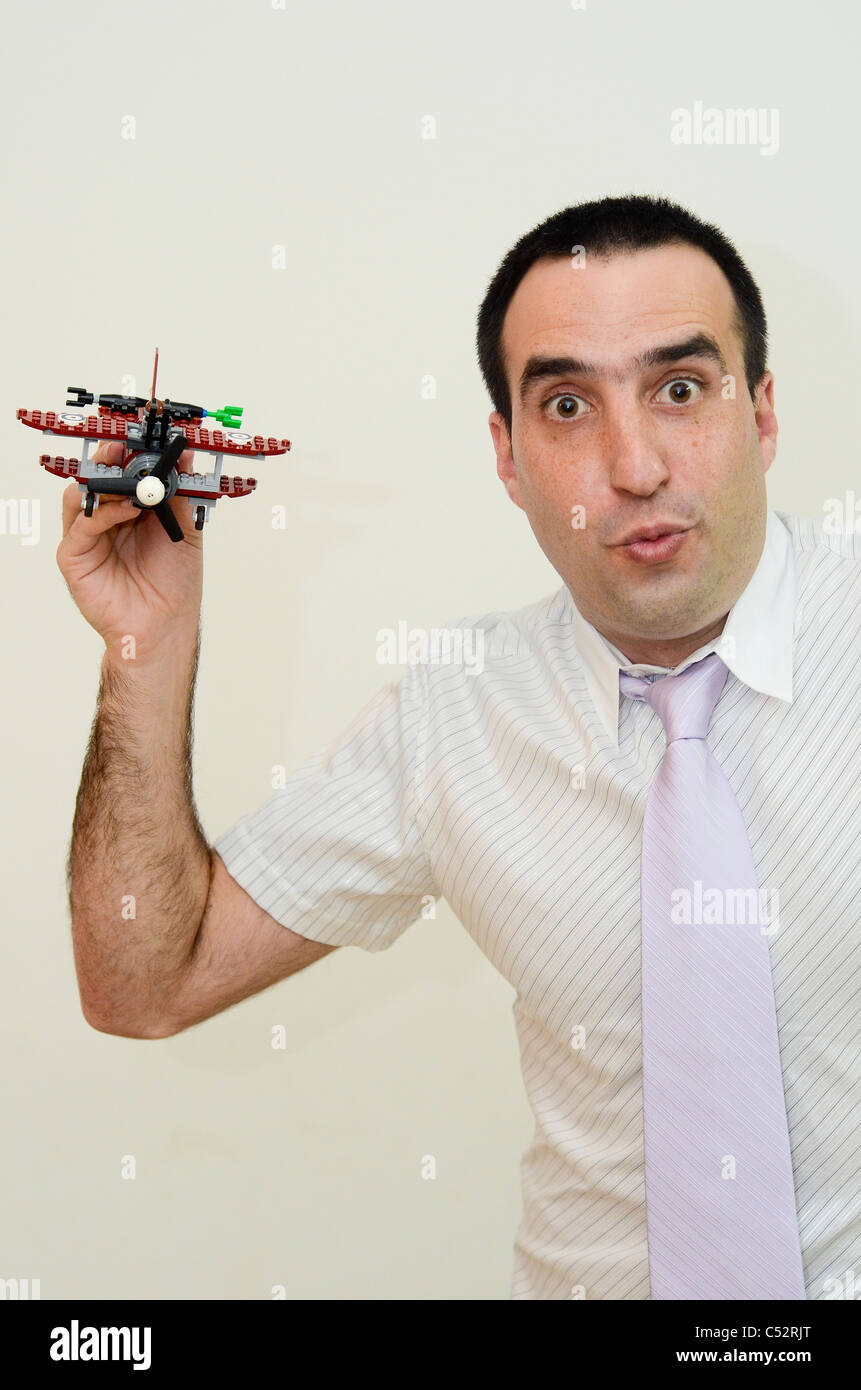 Young Man in his thirties with button down shirt and tie plays with a toy aeroplane - Stock Image