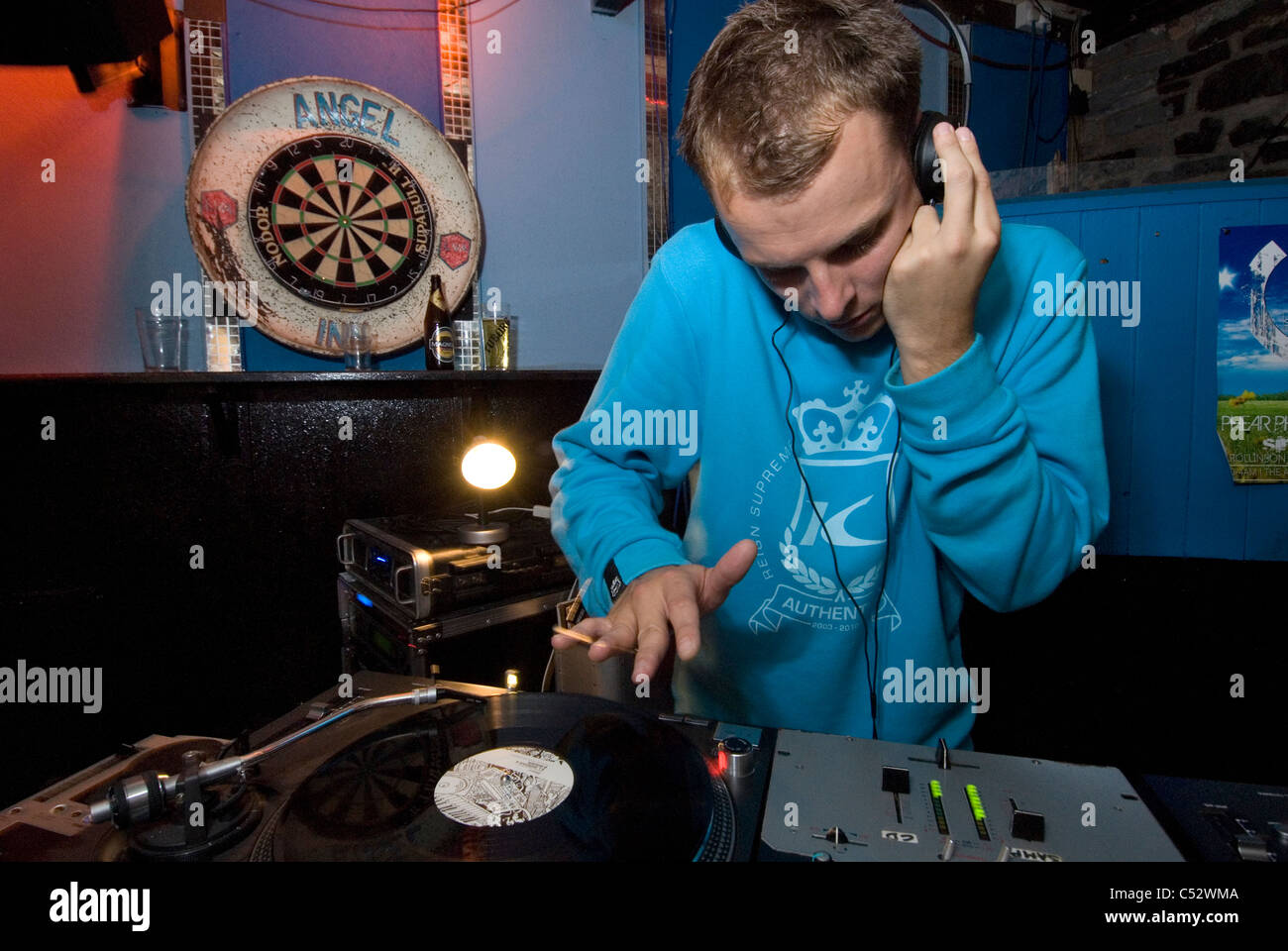 A young DJ scratching some vinyl on his decks - Stock Image
