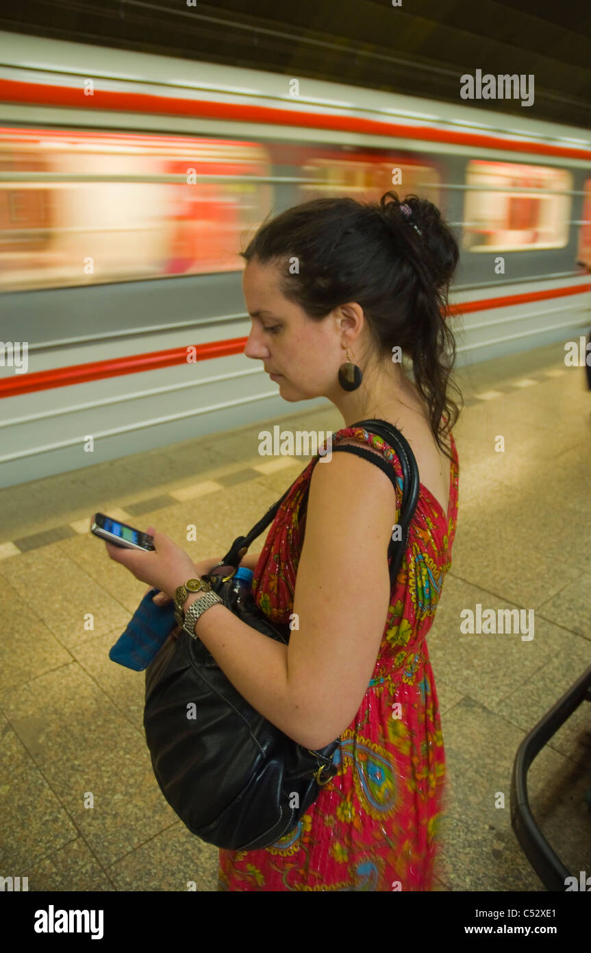 Woman in her late 20s using mobile phone at metro station Prague Czech Republic Europe - Stock Image