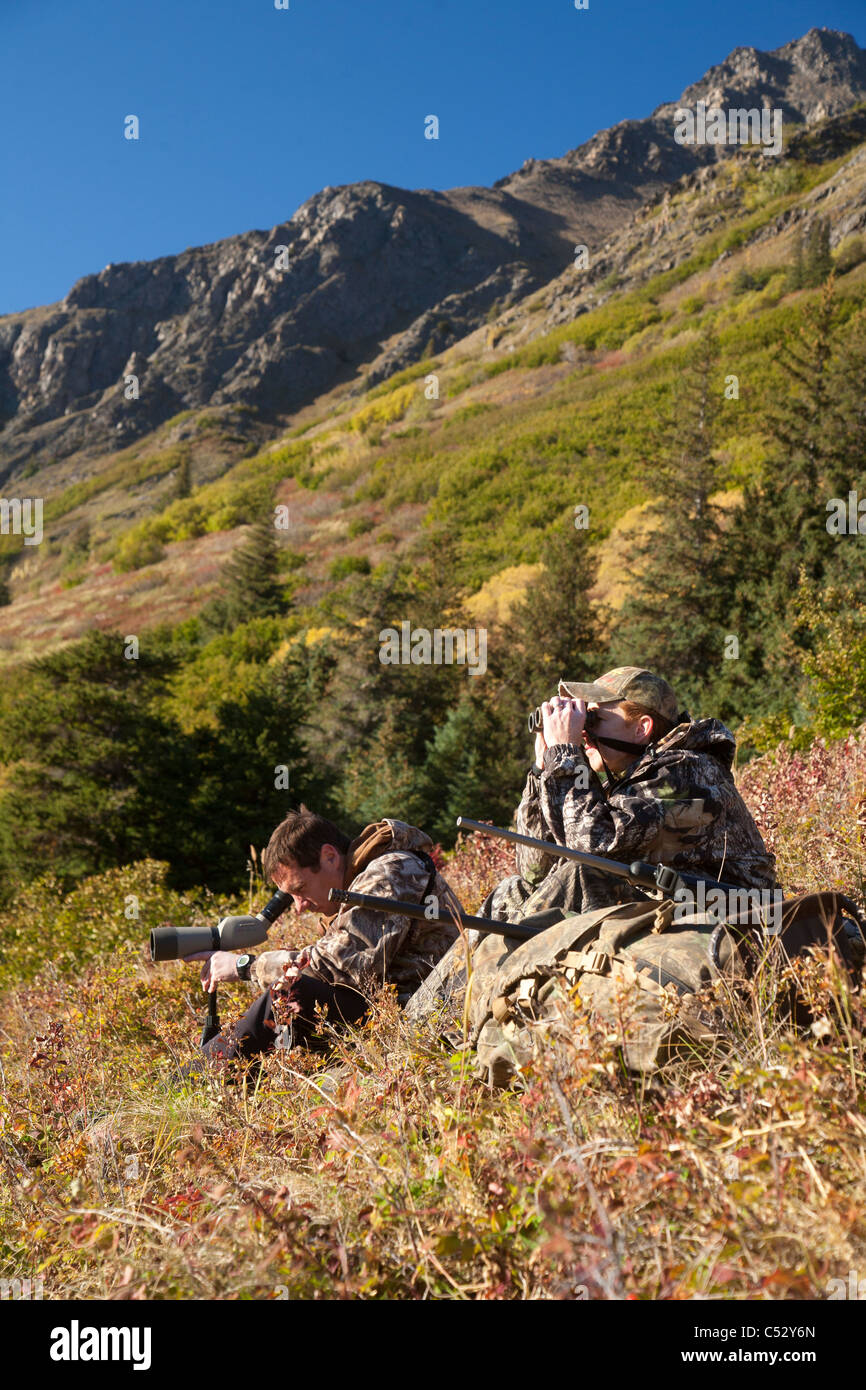 Two male moose hunters scope and glass for game, Bird Creek drainage area, Chugach Mountains, Chugach National Forest, - Stock Image