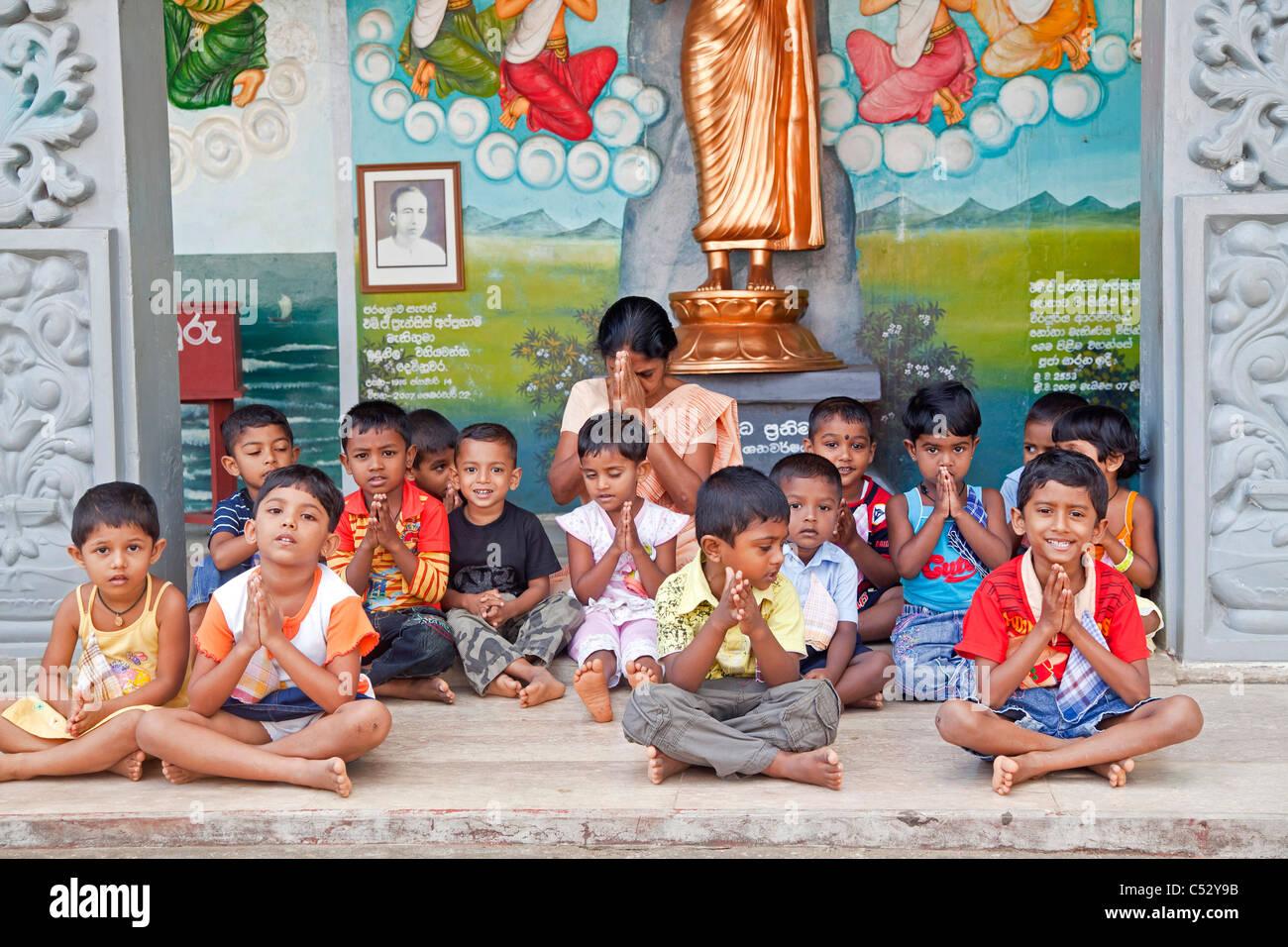 children and teacher praying in the Weherahena temple of Matara, Sri Lanka, Asia - Stock Image