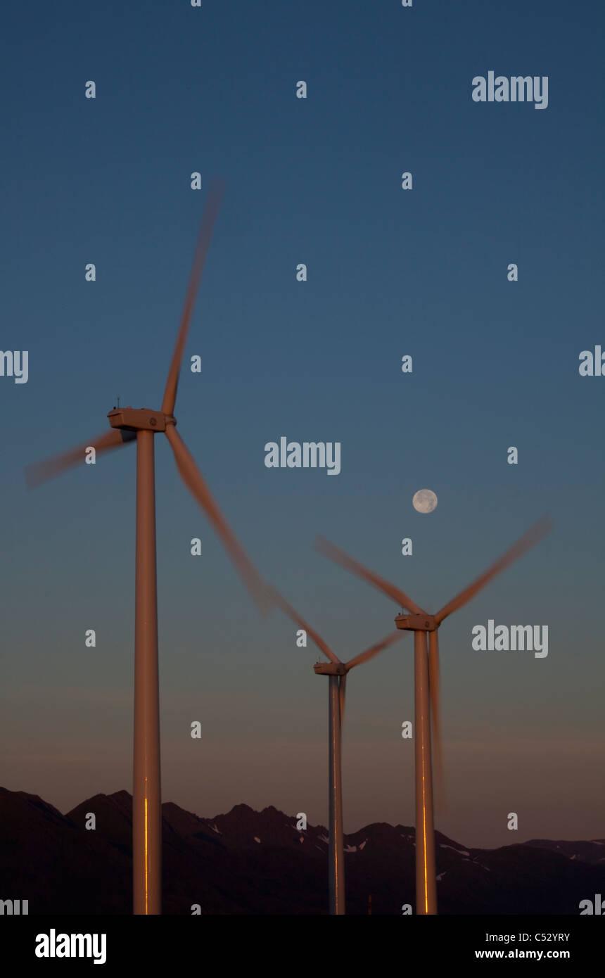 Pillar Mountain Wind Project wind turbines on Pillar Mountain at dawn with a full moon in the background, Kodiak Stock Photo