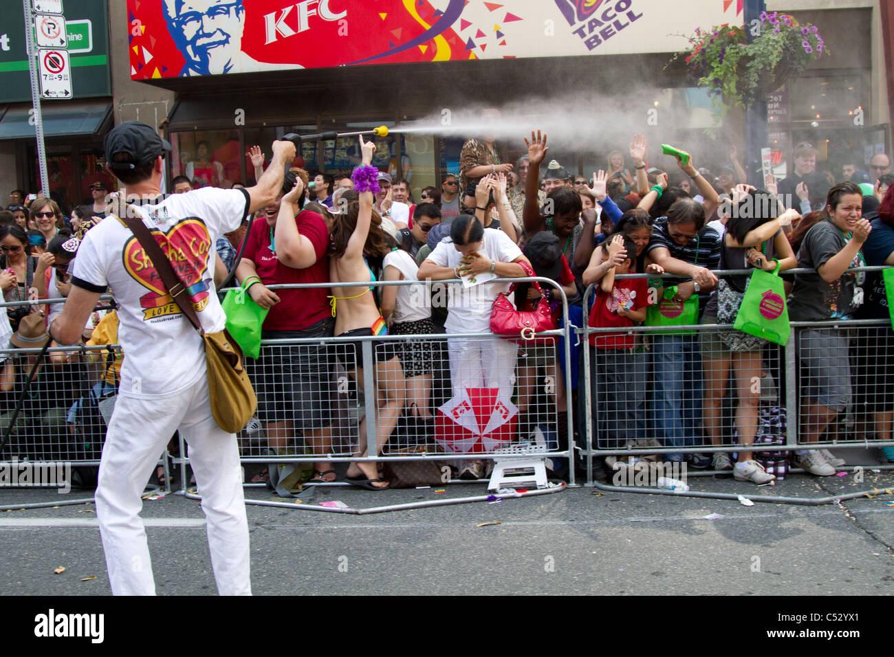 'water gun' splash splashing people pride parade - Stock Image