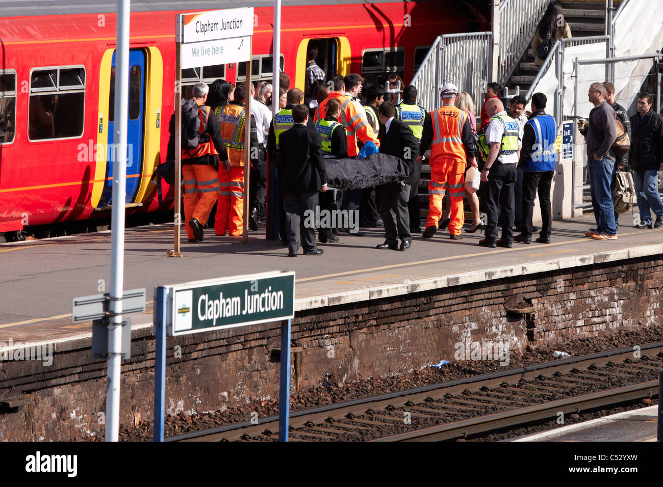 Undertakers recover the body of a suicide victim hit by a train at Clapham Junction - Stock Image
