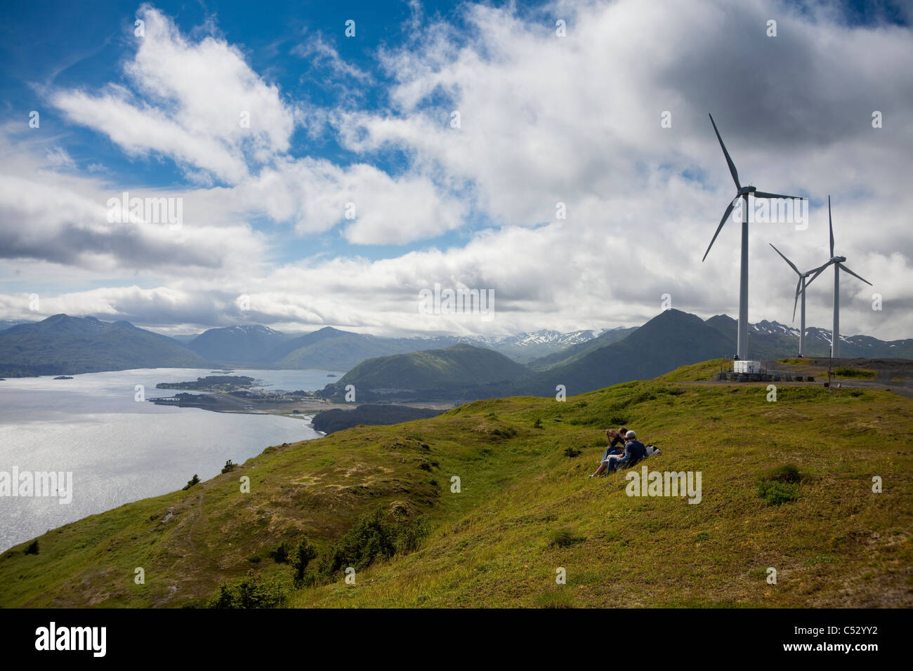 Hikers enjoying a sunny afternoon walk near the wind turbines, part of the Pillar Mountain Wind Project, Kodiak Stock Photo