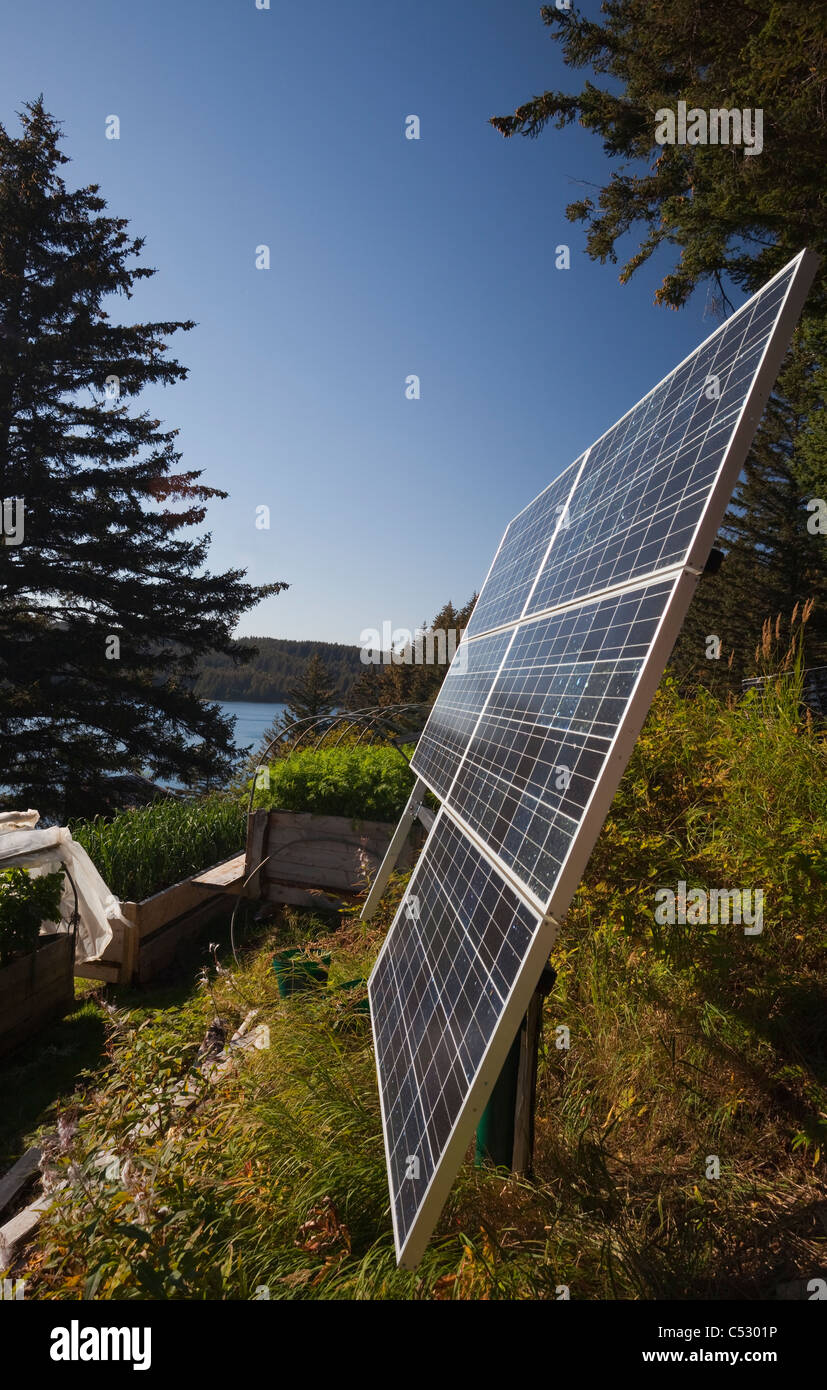 Close up of solar panels installed near a residential log cabin along the coastline, Kodiak Island archipelago, - Stock Image