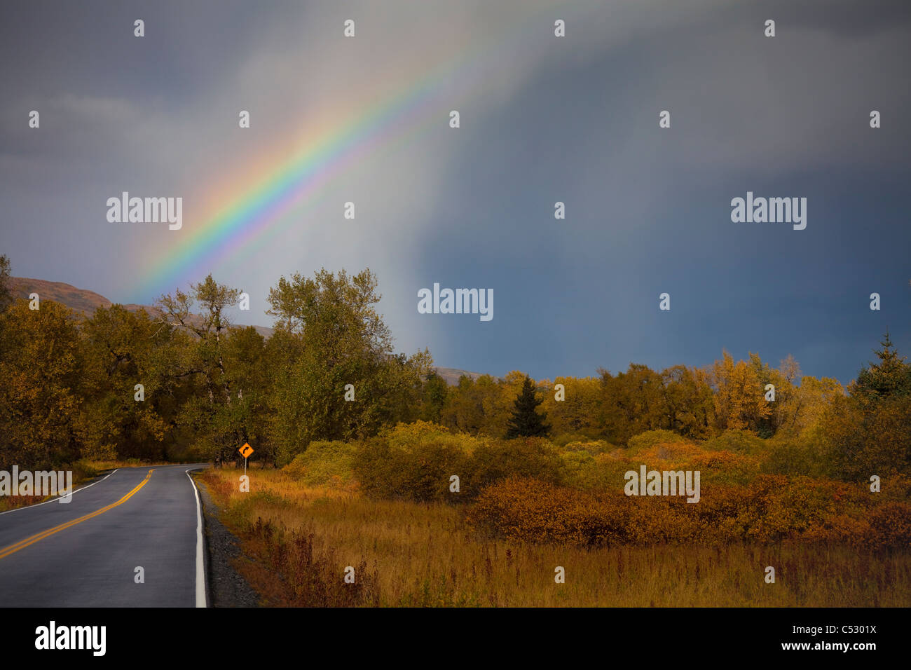 Scenic view of a rainbow and approaching squall above the Pasagshak Bay Road, Kodiak Island, Southwest Alaska, Fall - Stock Image
